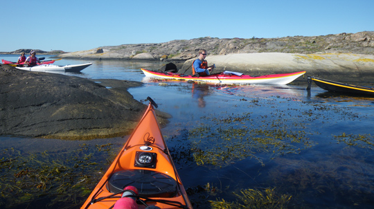 Me in my Romany surf kayak while the kayak is used to pass shallow water between some cliffs