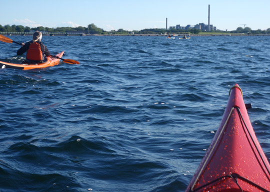 a photo of Anne-Grethe paddling her Tiderace with some KF Öresund kayakers visible further in front.