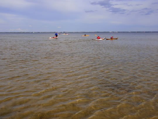 A number of kayaks on very shallow water, after 45 minutes walk on equally shallow water