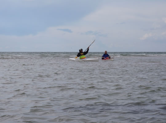 Kayak crossing from surf to shallow reef water