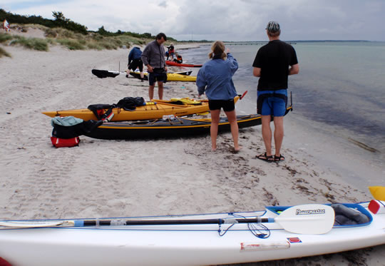 Kayaks and excursion members on the beach in front of Falsterbo House