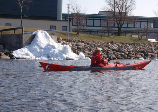 a kayak in malmoe harbour with some remnants of snow and some swahns
