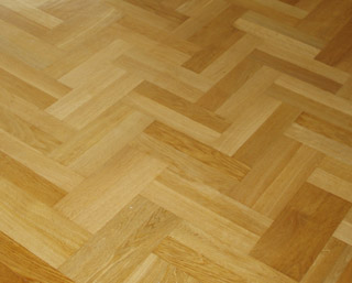 Gluing loose pieces of fishbone parquetry flooring back onto the floor